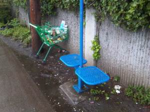 bus stop with shopping cart full of trash.
