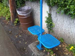 same bus stop with a trash barrel