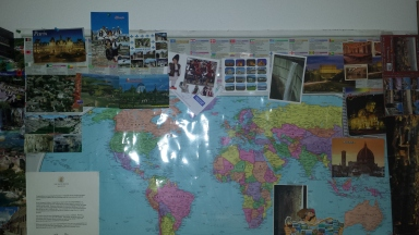 Postcards of the same size and shape above my desk from Albania, France, Italy, Romania, and an odd-shaped one from Bulgaria in the lower right.